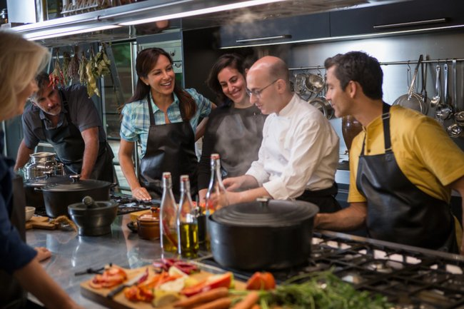Image of individuals in a kitchen learning how to cook