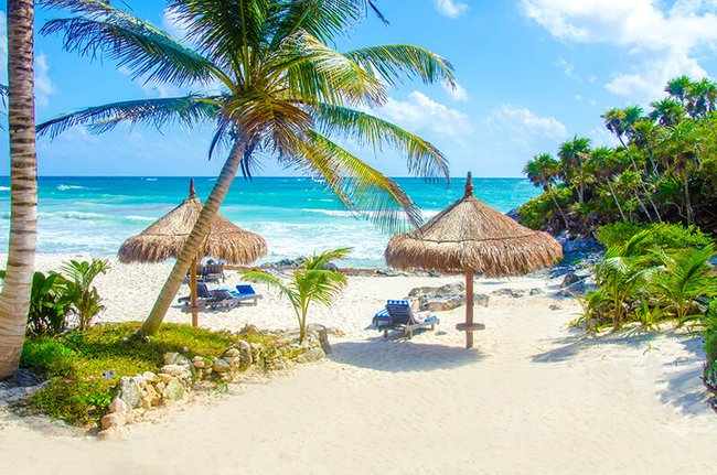 Tulum beach with thatch umbrellas and lounge chairs