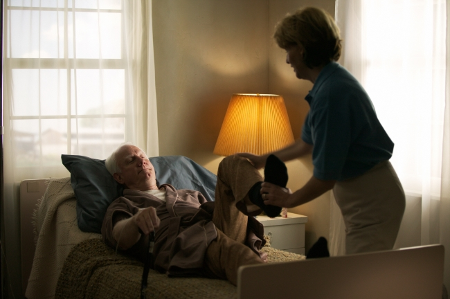 Home care nurse giving patient physical therapy