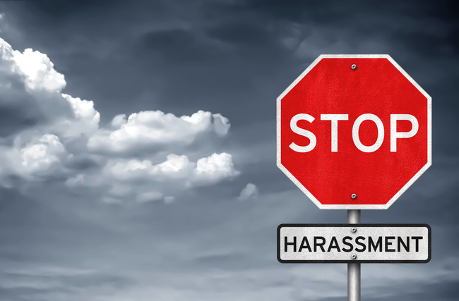 Stop sign with harassment sign underneath