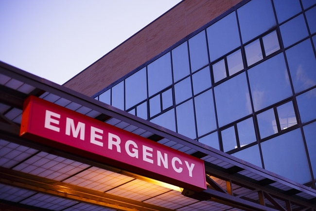 A lighted emergency room sign outside of a hospital